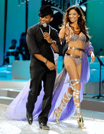 Usher strolls with Adriana Lima. With that hat, he's just about as tall as her.