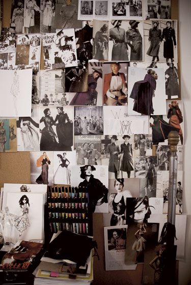 A wall of clippings, sketches, and photographs at the studio.