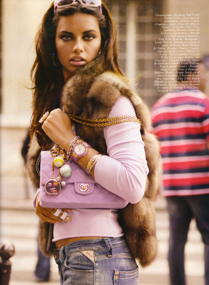 It's Adriana Lima not in a men's magazine! She's modeling accessories in a deliberately tacky spread in French <em>Vogue.</em> It kind of comes off as a Claire's catalogue, but she still looks smokin'.