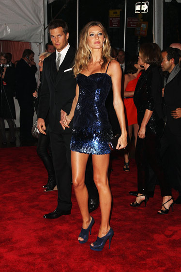 Gisele Bundchen in Versace dress, clutch, and shoes, with Tom Brady.