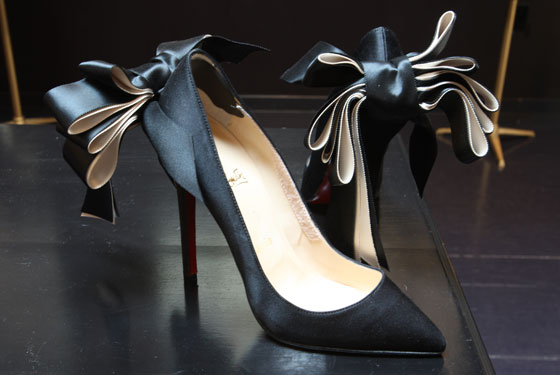 Black satin Christian Louboutin pumps with bows, $225.