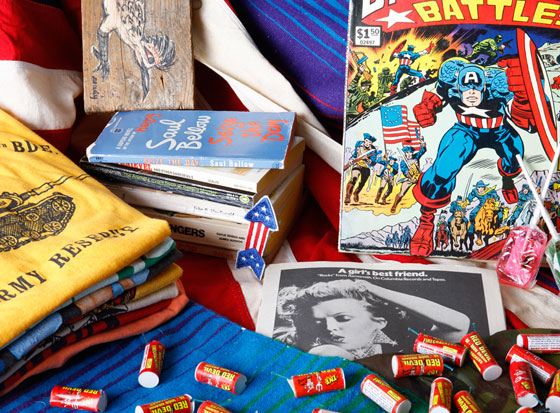An assortment of items up for sale, including comic books, T-shirts, red devils, and books.