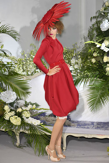 "In our fantasies, where life is like a <i>Dynasty</i> episode, we'd don this Dior for the funeral of our most hated, vicious nemeses, because nothing says ""I dance on your grave"" quite like a crimson dress and a hat that could give a bee the vapors. For the outfit alone we'd fork over our cars -- the reactions at the deli counter would be worth the hike to the supermarket -- but if Christian Dior could somehow provide the soapy double life too, we'd throw in every vehicle on our street and the hot tub next door."