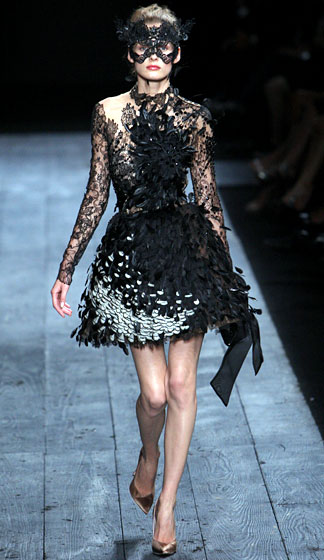 "We are not onboard with masks -- yet; get back to us the next time we have a zit on our foreheads -- but this intricate, edgy <a href=""http://nymag.com/fashion/fashionshows/2009/fall/main/europe/couturerunway/valentinocouture/"">Valentino</a> is an intriguing blend of Madonna and Marion Cotillard. If someone offered us the chance to test whether mere mortals can pull off this dress, we'd willingly wipe every one of Madge's songs from our iPods. That would make running 100 percent less bearable, but listen, she said it best herself: We are living in a material world, and we are material girls."