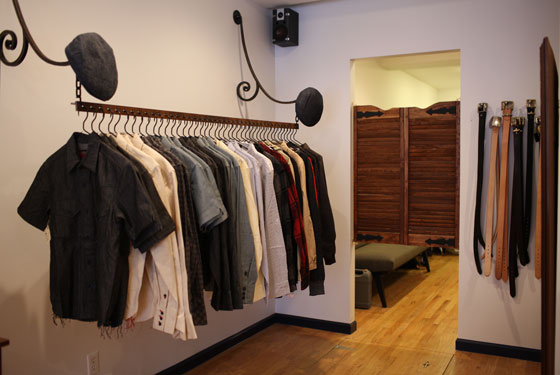 Button-downs and belts hang beside the dressing room.