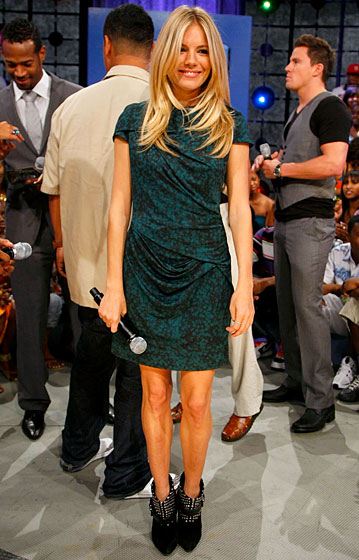 "Sienna's MO of late has been to wear a very simple dress and let her footwear do the talking. In this case, it's talking nonsense — they're a cross between ""fabulous"" and ""high-fashion ankle monitor"" — but the overall effect is fetching, and we wouldn't mind a crack at the dress to see if that draping is as flattering on everyone else as it is on Sienna's tiny frame. However, the crabby grandmother who lives in our psyche wants Sienna to flick that hair out of her face."