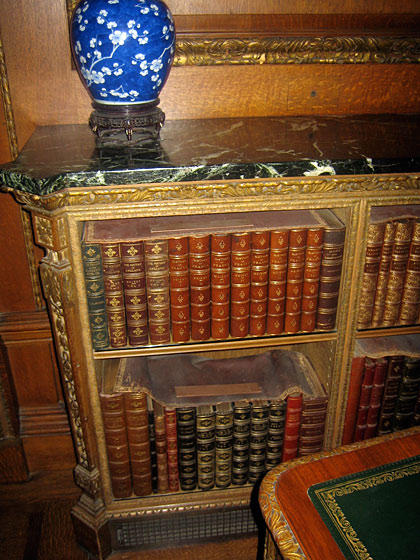 Mr. Frick had special leather covers made to protect his beloved books from collecting damaging dust (they are laying across the top of the leather-bound volumes).