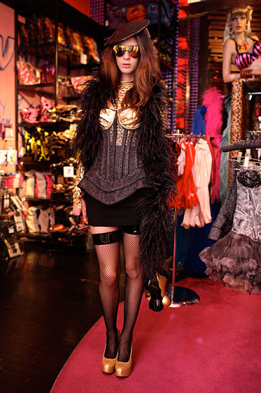Sales associates Moto and Reiko styled Coco in an outfit of Lady Gaga proportions. Our pencil skirt is barely recognizable under all those glittery layers, including an ostrich-feather boa ($85), Bordello Gold Fairy Dust platforms ($88), a Timmy Woods Adam and Eve purse ($260), vinyl top fishnet thigh highs ($14), MiniMini fingerless black leather gloves ($34), a Gasoline Glamour spike ring ($72), an Ophelie sequin UFO hat ($100), a Noir Keith Haring cuff ($168), Bernhard Willhelm ski glasses ($525), a V Moda hourglass corset ($770), and — lastly — a Natasha Midnight Raven bodysuit ($136).