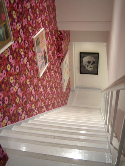 Damien Hirst's floral wallpaper lines the stairwell down to the gallery below the store, where there is more art for sale.