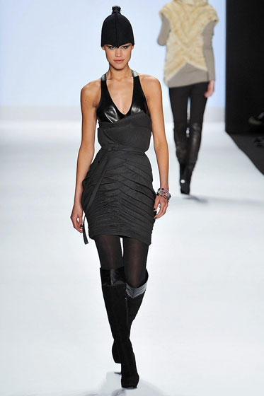 Okay, these beanies are freaking us out. They're like little black condoms atop the models' heads. This dress is sort of cool, but a little confused, though that's probably the point. The pleating on the bottom wouldn't flatter many figures, but the top leather area is well fit and striking.