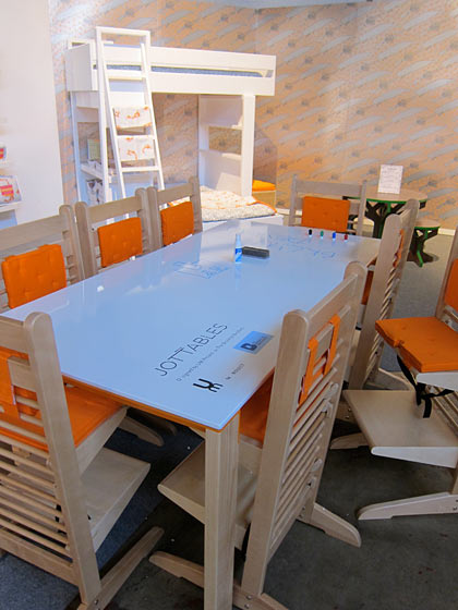 This is a table that would delight every kid! The markers are right there stored at the end so they can draw on the furniture. Isn't that always the best?