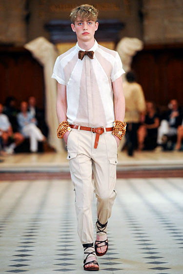 "The combination of this neutral sun-ray soda jerk top, emo-boy bow tie, knotted belt, and straight-ahead cargo pants tucked into espadrilles from <a href=""http://nymag.com/fashion/fashionshows/2011/spring/main/europe/menrunway/alexismabille/#slide7&ss1"">Alexis Mabille</a> is elegant in its simplicity. The armloads of beaded bracelets add a hippie-sweet touch."