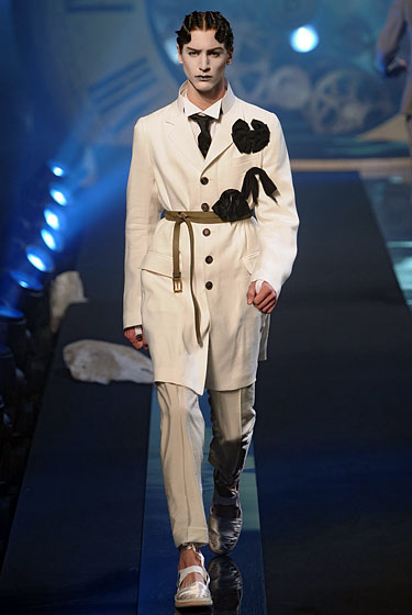 "From a theatrical standpoint, <a href=""http://nymag.com/fashion/fashionshows/2011/spring/main/europe/menrunway/johngalliano/#slide13&ss1"">John Galliano</a> can do no wrong, and neither can this belted waistcoat and florid brooch. (The mime paint and finger waves are another story ... )"