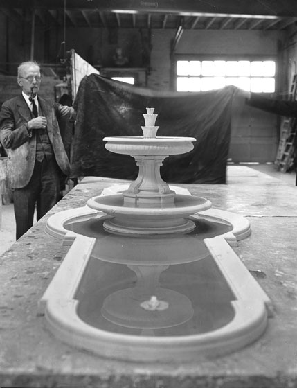 An unidentified man stands with a model of the courtyard fountain in Charles G. Peter's Long Island city studio.