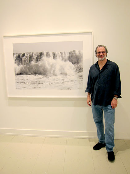 His pigment prints of ocean waves taken during a hurricane in 2009 are so powerful that you feel as if you might be swept away when standing in front of them. Ross, pictured here, <em>practically</em> was — he had to be tethered to a group of friends on shore when he took these photographs standing waist-high in the water.
