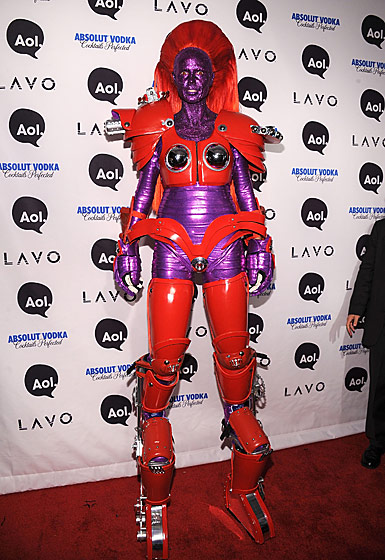 "Of course the woman who any <em>Redbook</em> editor will tell you can do it all and has it all can also walk on stilts. See how short the plebeian on the right is next to her? She could crush him! With her <a href=""http://nymag.com/daily/fashion/2010/10/runway_slideshow.html"">boob patches</a>!"