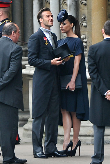 Victoria Beckham in a Victoria Beckham dress, Philip Treacy hat, and Christian Louboutin shoes; David Beckham in Ralph Lauren.