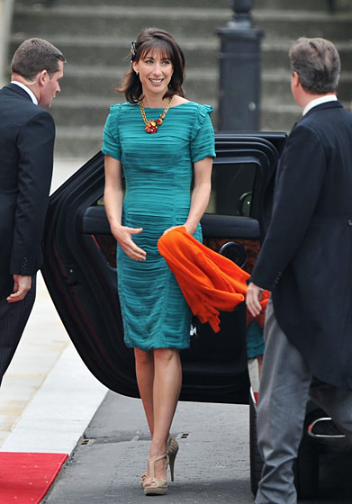 Samantha Cameron in a dress by Burberry, scarf by Erickson Beamon for Erdem, necklace by Erickson Beamon, and shoes by Aldo.