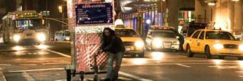 Man pulling food cart down an avenue in Manhattan.