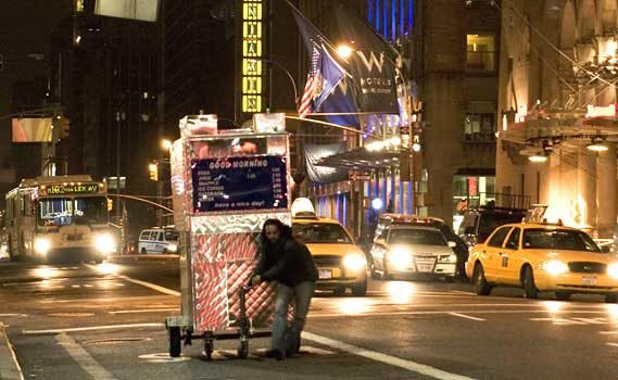 Man pulling food cart down an avenue in Manhattan