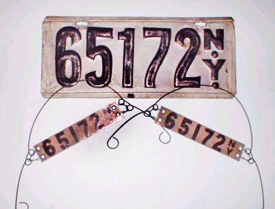 New York is the first state in the union to require license plates. For the first few years, drivers have to supply (and often make) their own. Nothing's standardized, and materials vary widely, from metal to wood to leather. This one, from 1906, was homemade, and is attached to two smaller tags placed elsewhere on the car. <br>