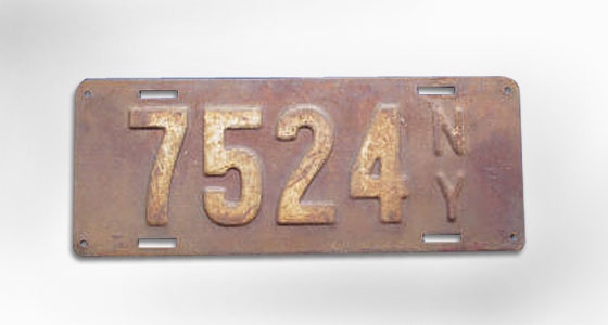 Our first state-issued plates. They're smaller than today's, but surprisingly familiar nonetheless: stamped steel, raised numerals, blue paint with white digits. The next year, they're changed to maroon-and-white (pictured). <br>
