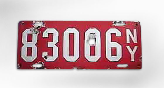 For one year, New York (like many other states) makes its plates from porcelain enamel over metal, now with letters as well as numbers. Pretty elegant, for a license plate — but too fragile for early roads full of pebbles and debris. <br>