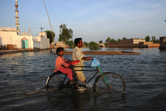 A Pakistani man and his daughter make their way through the floods.