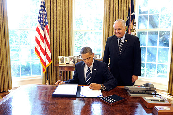 Texas congressman Silvestre Reyes is trying not to giggle as he silently stands behind President Obama, hard at work at his desk.