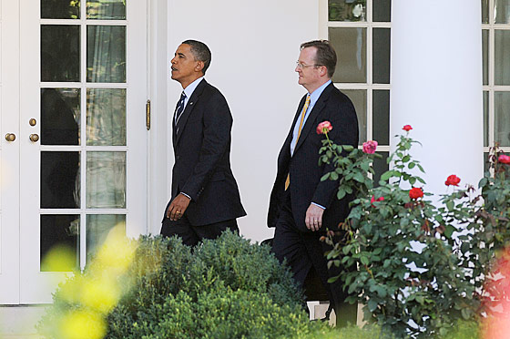 An amused Robert Gibbs tries to see how close he can get behind Obama without being caught.