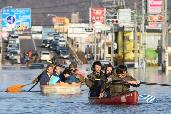 Survivors paddle through the streets in Ishinomaki.