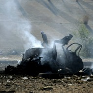 A Libyan rebel walks past burnt-out vehicle belonging to Qaddafi supporters.